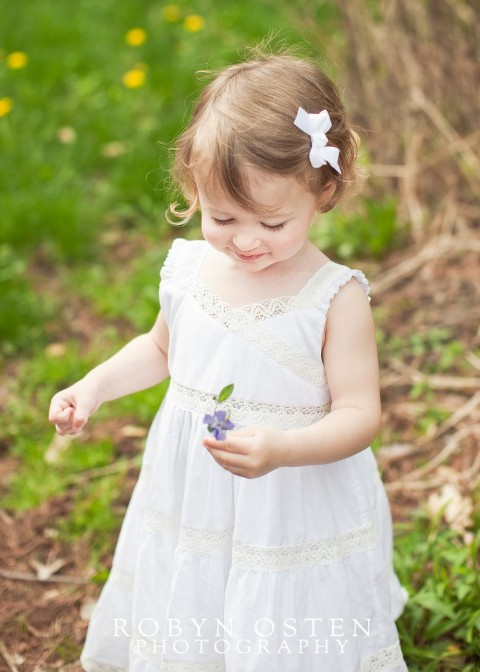 little girl in white dress looking down at flower for outdoor spring portraits in maryland -