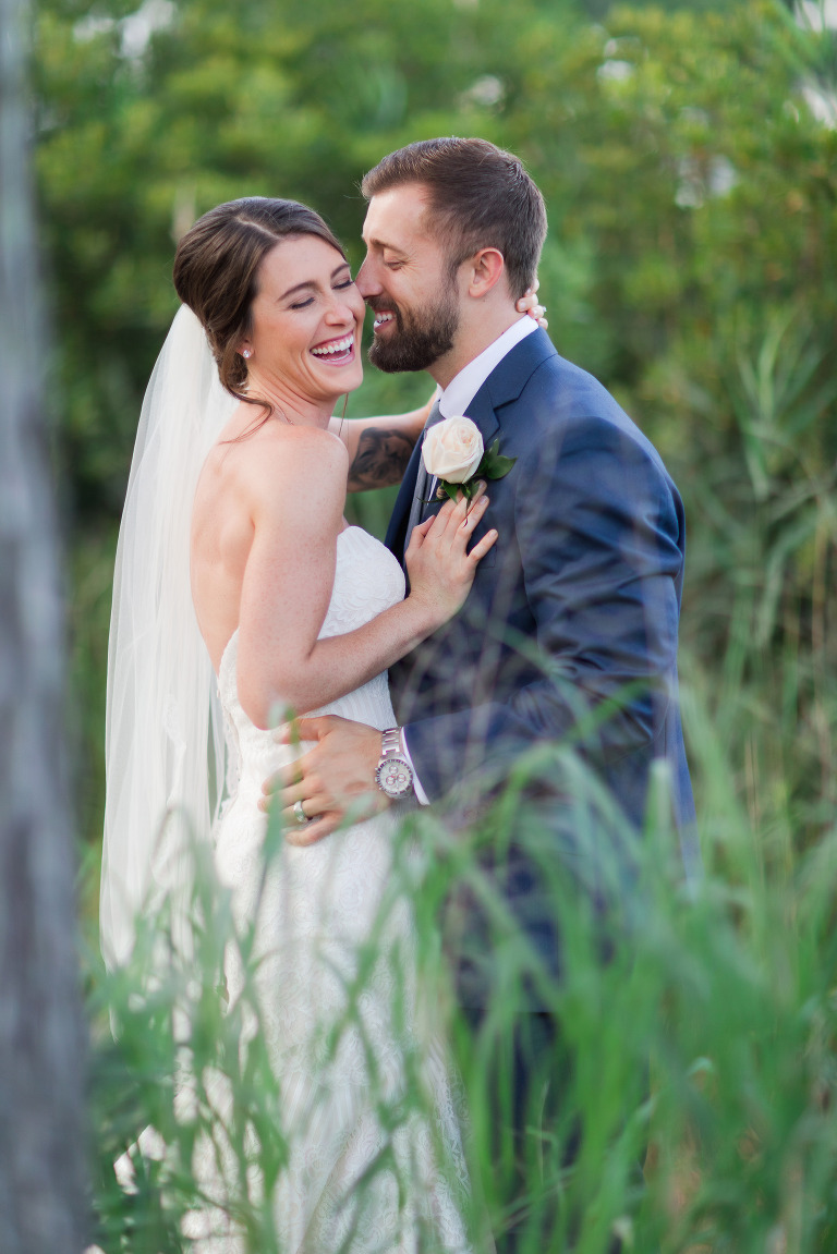 bride and groom laughing in the tall grass portrait